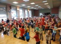 dzieci wraz z nauczycielami stoją bokiem i machają rękami w rytm muzyki