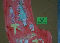 czerwona skarpeta ozdobiona choinkami i podobiznami gwiazdora narysowanymi przez dzieci