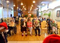 Oświetlona sala, na krzesłach i wózkach inwalidzkich siedzą seniorzy i oczekują na koncert