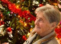 Uśmiechnięta starsza pani na tle przystrojonej choinki