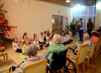 Dzieci z muzykowa podczas koncertu, seniorzy przysłuchują się śpiewowi kolęd