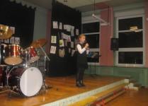 Dziewczynka w czarnej sukience śpiewa na scenie