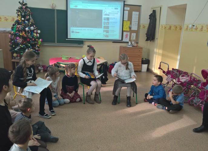 Dzieci siedzą w kole starsze koleżanki czytają dzieciom z oddziału przedszkolnego