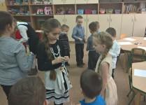 DZieci z klasy 3B przyklejają młodszym kolegom naklejki-nagrody