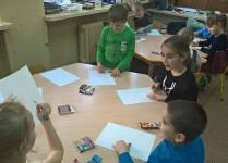 Dzieci siedzą przy stolikach i wykonują ilustracje, pomaga im starsza koleżanka