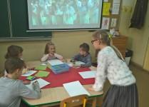 Dzieci z oddziału przedszkolnego siedzą przy stoliku i rozmawiają z koleżanką z klasy 3B