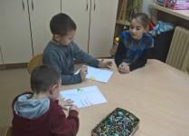 Dzieci z oddziału przedszkolnego wykonują ilustracje pod czujnym okiem starszej koleżanki