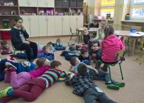 Dzieci z oddziału przedszkolnego leżą na dywanie, starsze koleżanki czytają im książkę