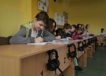 uczniowie pracujący w czasie lekcji języka angielskiego, przy każdym stanowisku zestaw słuchawkowy