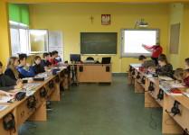 rzut z tyłu na pracownię językową, widoczna tablica, tablica interaktywna i stanowiska uczniowskie