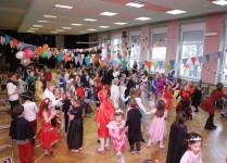 przystrojona balonami aula szkolna pełna dzieci w strojach karnawałowych
