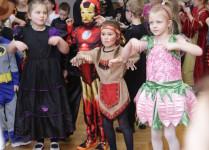 Grupa dzieci w strojach karnawałowych ćwiczy układ taneczny
