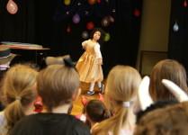 """dziewczynka w złotej sukience tańczy na scenie """"balet"""""""