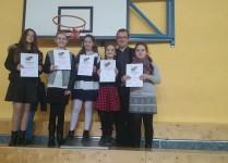 Na scenie stoi pięć dziewczynek wraz z nauczycielem muzyki. DZiewczynki trzymają w rękach dyplomy za uczestnictwo w konkursie