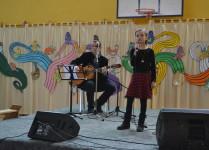 Zwyciężczyni konkursu w czarnej bluzce i spódniczce w czarno-czerwoną kratę śpiewa piosenkę z lewej strony nauczyciel akomaniujący na gotarze. W tle dekoracje w kolorowe nuty i pięciolinie