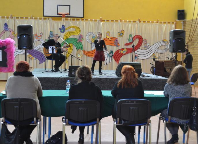 Jury siedzi tyłem i wsłucha występu dziewczynki ubranej w czarną bluzkę i spódniczkę w czarno-czerwoną kratę, z lewej strony akompanijący na gitarze nauczyciel muzyki. W tle kolorowe dekoracje.