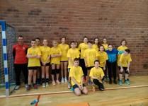 Drużyna dziewczynek i chłopców w żółtych koszulkach pozuje do zdjęcia z trenerami