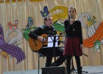 DZiewczynka w czarnej bluzce śpiewa w duecie z nauczycielem muzyki, który akompaniuje na gitarze.