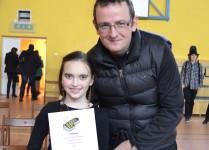 Zwyciężczynki konkursu pozuje do zdjęcia z nauczycielem muzyki. W ręce trzyma dyplom.