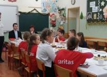 Dzieci w czerwonych koszulkach z logo Caritas siedzą przy stole