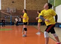 Sala gimnastyczna, na pierszym planie dziewczynka w żółtej koszulce szykuje się do wyskoku, w tle inn dziewczynki w żółtych koszulkach