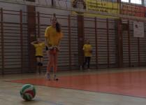 Sala gimnastyczna, dziewczynki w żółtych koszulkach trenują zagrywkę, w tle drabinki