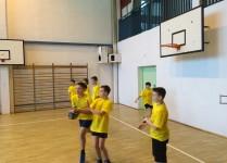 Chłopcy w żółtych koszulkach trenują zagrywkę