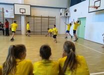 Sala gimnastyczna, chłopcy w żółtych koszulkach przygotowują się do meczu, przyglądaja im się koleżanki