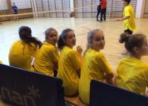 Dziewczynki w żółtych koszulkach siedzą na ławce w oczekiwaniu na mecz swoich kolegów