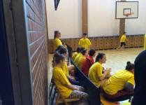 Drużyny chłopców i dziewczynek wraz z trenerem siedzą na łąwkach w oczekiwaniu na swój występ
