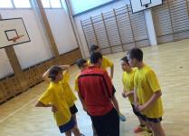 Chłopcy w żółtych kouklach stoją w kole razem z trenerem, który udziela im ostatnich wskazówek