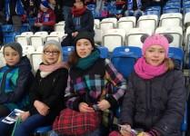 tRzy dziewczynki i jeden chłopiec z policzkami umalowanymi w barwy Lecha poznań siedzą na stadionie