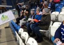 Dzieci ubrane w szaliki Lecha Poznań siedzą na trybunach czekając na mecz