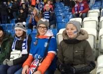 Trzy dziewczynki w koszulkach i szalikach Lecha oraz twarzami pomalowanymi w niebiesko-białe barwy