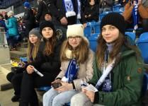 Cztery dziewczynki w szalikach Kolejorza siedzą na trybunach w oczekiwaniu na mecz