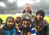 Dwie dziewczynki i dwóch chłopców pozują do zdjęć z piłkarzem Nicki Bille Nielsenem w tle widać trybuny i murawę stadionu