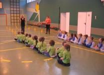 dzieci siedzące w rzędach na sali gimastycznej słuchają zasad zawodów