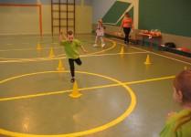 chłopiec w zielonej koszulce skacze na jednej nodze między żółtymi pachołkami