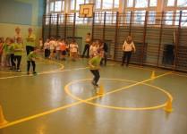 chłopiec biegnie z pałeczką sztafetową między żółtymi pachołkami, w tle widać dzieci ustawione w rzędach