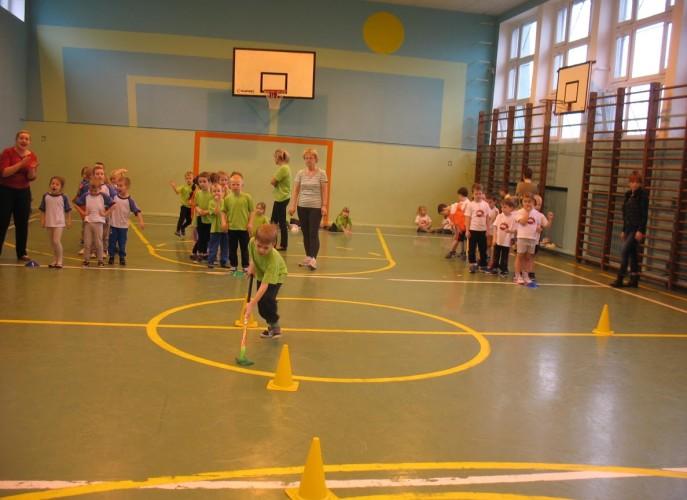 trzy rzędy dzieci, na pierwszym planie chłopiec w zielonej koszulce prowadzi kijem hokejowym woreczek z grochem między żółtymi pachołkami