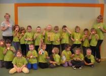 Grupa przedszkolaków ustawiona do zdjęcia z wychowawczyniami. Dzieci i panie w zielonych koszulkach. Każde dziecko na szyi ma medal.