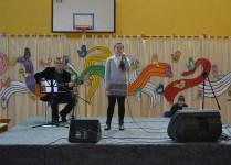 Na scenie dziewczynka w szarej sukience śpiewa do mikrofony, z lewej strony nauczyciel muzyki akompaniuje wolakistce na gitarze, w tle kolorowe dekoracje w nuty i pięciolinie