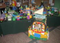 """Wystawa prac konkursowych """"Zabawka z nieużytków"""" wśród nich: wyścigówka z kartonów i nakrętek, lalki z tektury, robot z pojelników na jajka, zwierzęta z papieru"""
