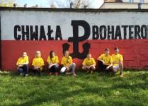 """Uczniowie z naszej szkoły w żółtych koszulkach przykucnięci na trawie. Za nimi mur pomalowany na biało-czerwono i napis """"Chwała bohaterom"""" po środku znak Polski Walczącej"""