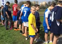 Chłopcy na starcie biegu. Na środku chłopiec w żółtej koszulce.