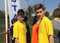 Dwóch chłopców w żółtych koszulkach na starcie biegu.