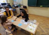Sala lekcyjna. Dziewczynka wraz z nauczycielkami gra w gry logopedyczne