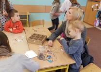 Warsztaty robienia biżuterii. Na stolikach leżą kolorowe koraliki, dzieci robią branzoletki.