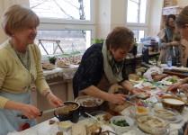 Szkolna spiżarnia. Nauczycielki komponują kanapki ze smalcem, pastami rybnimi, jajecznymi i innymi. Na stołach rozstawione produkty: domowy chleb, smalec, pasty, szczypiorek, żeżucha i inne.