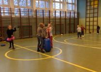 Dzieci w sali gimnastyczne biorą udział w zabawach ruchowych